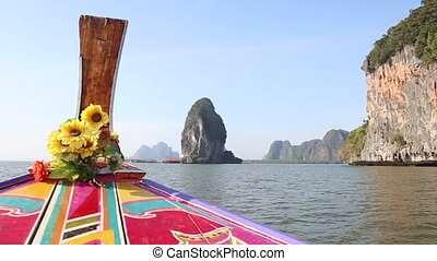 ornamented longtail boat sails up to village near cliff