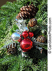 Ornaments and pine cones among evergreen branches.