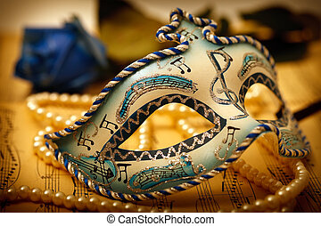 Ornate carnival mask on a music paper with rose and pearl