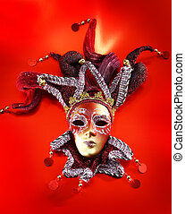 Ornate carnival mask over red background.