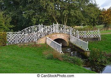 Ornate iron bridge over small stream