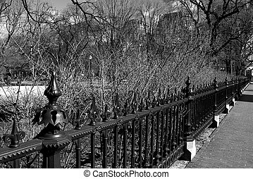 Ornate wrought iron fence running along the public garden with a brick sidewalk.