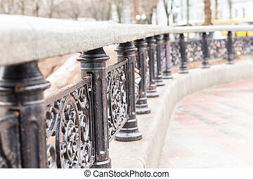 Ornate wrought iron railings curving around the edge of a...