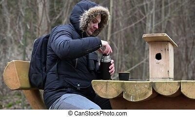 Ornithologist drink tea near table