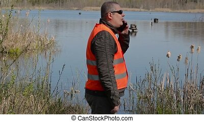 Ornithologist near the duck's houses at the lake