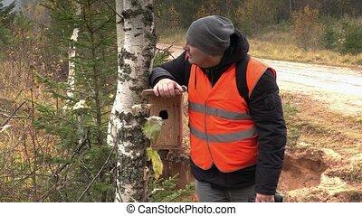 Ornithologist using binoculars in forest
