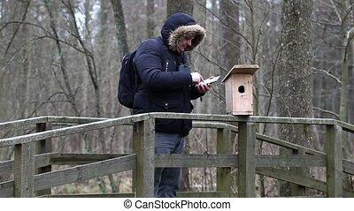 Ornithologist using tablet PC near bird cage