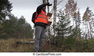 Ornithologist with binoculars and bird nesting box
