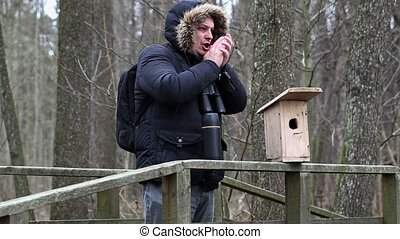 Ornithologist with binoculars on the bridge near bird cage