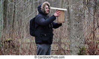 Ornithologist with bird cage near tree