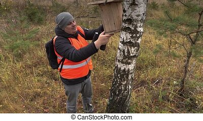 Ornithologist with  bird nesting box near birch in forest