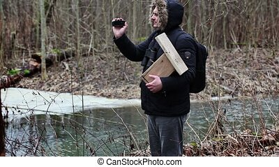 Ornithologist with camcorder and bird cage