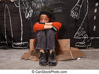Orphan child on the street concept - boy sitting by the wall with drawn parent figures