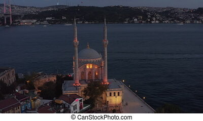 Ortakoy Mosque illuminated in beautiful yellow light on Water side at Dusk with Bosphorus and Bridge, Aerial wide shot