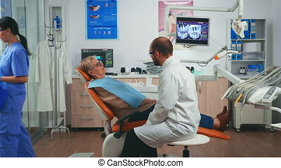 Orthodontist discussing MRI scan with patient sitting in stomatological chair in dental clinic. Elderly woman explaining dental problem to doctor indicating mouth while nurse working in background