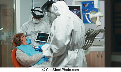 Dentist in coverall using tablet explaining dental x ray to patient in stomatologic office during coronavirus. Man wearing face shield, coverall, mask showing to woman radiography using digital device