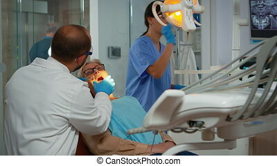 Orthodontist lighting the lamp until examination and patient opening mouth. Stomatologist speaking to woman with toothache sitting on stomatological chair while nurse preparing tools for surgery.