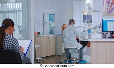Orthodontist lighting the lamp until examinating elderly woman while patients waiting in reception area filling dental form. Dentist speaking to woman with toothache sitting on stomatological chair.