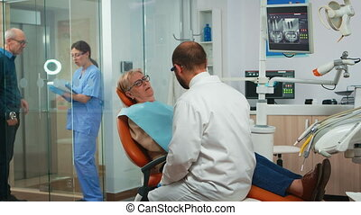 Orthodontist speaking to patient with toothache sitting on dental chair preparing for examination. Elderly woman talking with dentistry doctor while nurse working on computer in background.