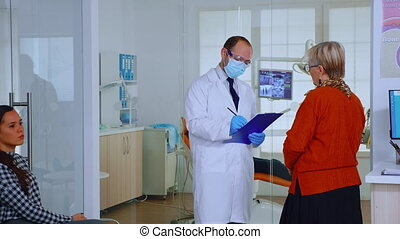 Orthodontist with mask speaking with elderly woman standing in waiting area of stomatological clinic taking notes on clipboard while nurse typing on computer appointments in modern crowded office.