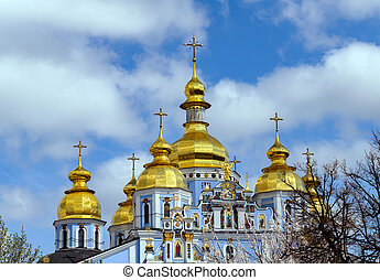 Orthodox Christian Cathedral with golden domes and crosses against the sky, spring day
