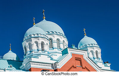 Orthodox Church with swans on the sky background