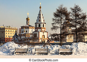 Orthodox churches, built in the early nineteenth century behind three empty benches. Siberia, Russia