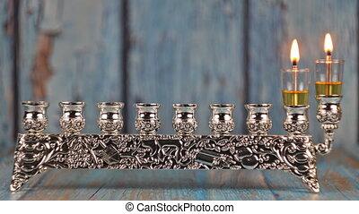 Orthodox jewish light a hanukkah menorah with candles. - ...