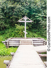 Orthodox wooden cross in the territory of the holy spring Gremyachiy key. Moscow region