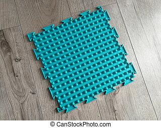 Orthopedic mat for feet massage on the wooden floor