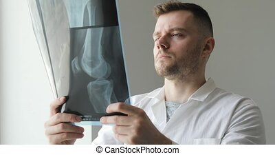 Orthopedist is learning bones on x-ray images standing near ...