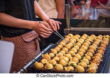 Osaka, Japan Okonomiyaki - Takoyaki being prepared at a ...