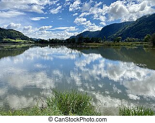 Ossiacher Lake in Carinthia, Austria on a summer day with great cloudscape being reflected in the Lake