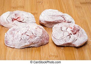 ossobuco floury (bone-in lamb shank steaks) on a wooden chopping board