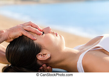 Osteopath doing cranial manipulation on woman outdoors.