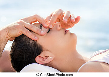 Osteopath doing facial therapy on woman outdoors.