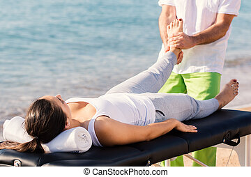 Osteopath doing foot therapy on female foot outdoors.
