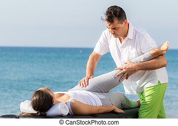 Osteopath doing hip and leg treatment outdoors on patient.