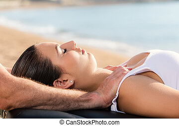 Osteopath doing shoulder treatment on woman outdoors.