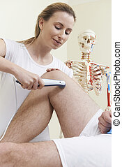 Osteopath Giving Ultrasound Treatment To Male Client With Sports