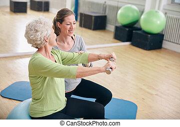 oude vrouw, geassisteerd, door, persoonlijke trainer, in, gym