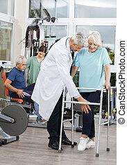 oude vrouw, gebruik, walker, terwijl, geassisteerd, door, mannelijke arts
