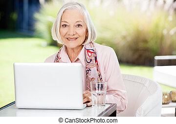 oude vrouw, gebruikende laptop, op, verpleeghuis, portiek