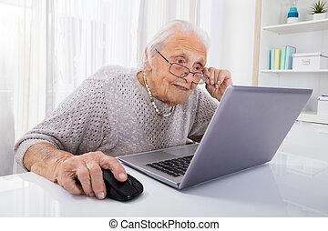 oude vrouw, gebruikende laptop