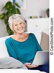 oude vrouw, gebruikende laptop, terwijl, zitten op sofa