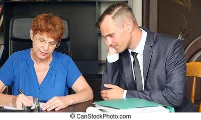 oude vrouw, handtekening, vorige wens en testament, zittende , op, desk., de, persoon, in, de, kostuum, zit, naast, haar, en, adviseert, haar., 4k, slowmotion