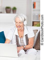 oude vrouw, het dragen van hoofdtelefoon, terwijl, gebruikende laptop, op, sofa