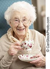 oude vrouw, het genieten van, kop van thee, thuis