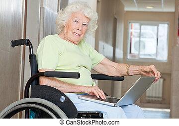 oude vrouw, in, wheelchair, gebruikende laptop