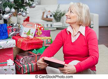 oude vrouw, met, kerstkado, kijken weg